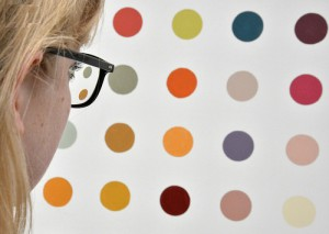 A visitor looking at one of the works from the series Spin Painting by British artist Damien Hirst at the gallery Tate Modern in London