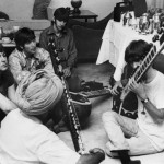 George Harrison as he receives instruction in playing the 'sitaar' from a turbaned Sikh teacher as the other members of the Beatles look on in quiet fascination