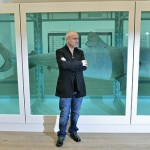 British artist Damien Hirst poses beside his work, tiger shark in an aquarium with formaldehyde