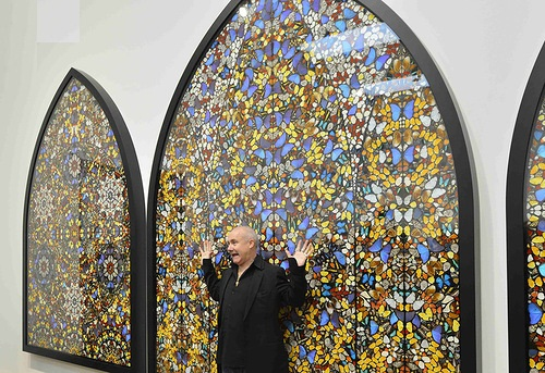 British artist Damien Hirst poses in front of his triptych Doorways to the Kingdom of Heaven in the gallery Tate Modern in London.