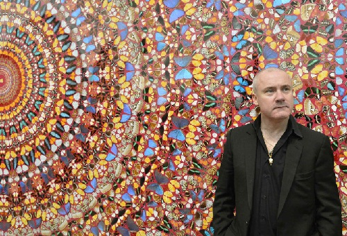 British artist Damien Hirst posing in front of his triptych Doorways to the Kingdom of Heaven in the gallery Tate Modern in London.