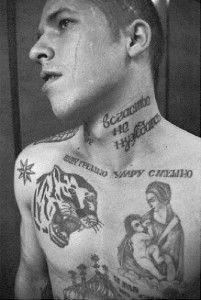 The tattoo on the neck reads 'I don't need happiness', beneath the neck 'I live in sin, I die laughing'.