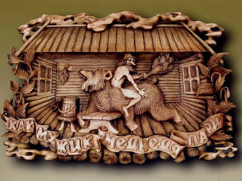 Folk motif - a man and a bear in banya. Wood carving by Russian artist Peter Nosikov