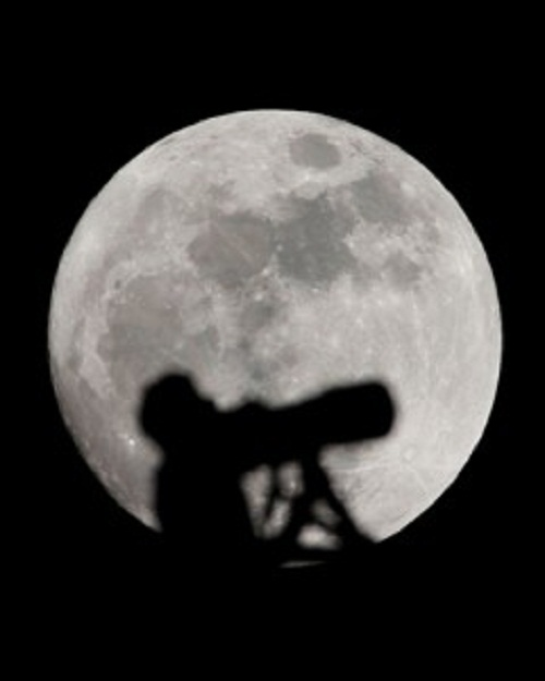 An amateur astronomer observes the super moon in Wuhan, capital of central China's Hubei Province