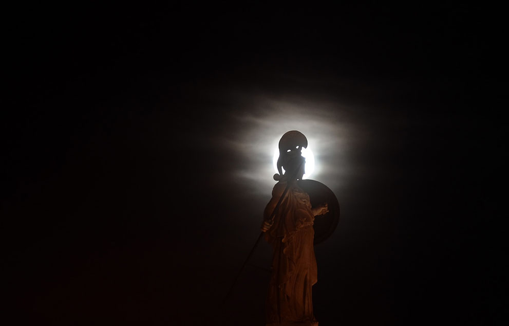 Ancient statue of the goddess Athena on the background of the full moon in Athens, Greece.