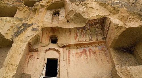 Rather than clinging to it, this temple was carved into the rock in the region of Cappadocia in Turkey. Frescoes can be seen around the entrance