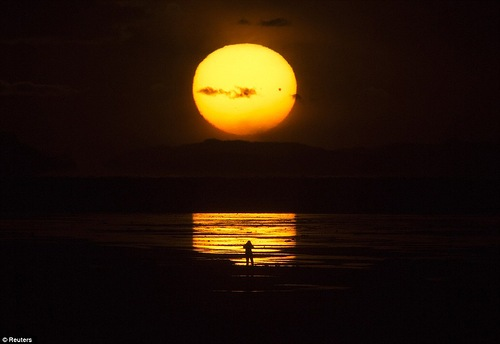 The planet Venus makes a transit as a person watches the sun set over the Great Salt Lake outside Salt Lake City, Utah, June 5, 2012