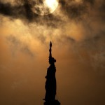 The planet Venus passes in front of the sun as it begins to set behind the Goddess of Liberty atop the Texas State Capitol in Austin, Texas