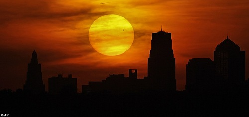 Venus silhouetted as it crosses in front of the sun as it sets behind the Kansas City, Missouri skyline on Tuesday, June 5, 2012