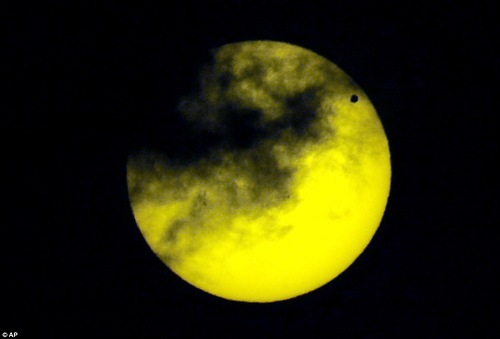 Venus, upper right, transits the sun as seen through a dark glass from Quito, Ecuador, Tuesday, June 5, 2012