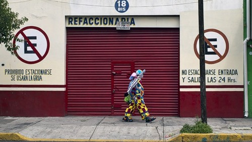 A clown passes in front of a closed store as he arrives to take part in the pilgrimage to the Virgin of Guadalupe's basilica, Mexico's patron saint, in Mexico City on July 18, 2012. Hundreds of clowns take part in the annual pilgrimage to the sanctuary of the Virgin.