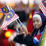 A girl waves a national flag in a parade during the celebration of National Independence Day in Kuala Lumpur, Malaysia