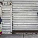 A man looks at a clown as he walks past a closed store while arriving to take part in a pilgrimage to the Virgin of Guadalupe's basilica, Mexico's patron saint, in Mexico City on July 18, 2012. Hundreds of clowns take part in the annual pilgrimage to the sanctuary of the Virgin.