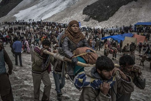 A Hindu pilgrim is carried on a palanquin by Kashmiri bearers over a glacier on her way to the sacred Amarnath Cave, one of the most revered Hindu shrines, on June 29, 2012 near Baltal, Kashmir, India