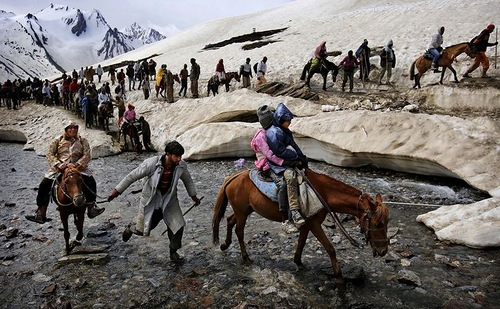 A Kashmiri horseman leads pilgrims on horseback across a stream during the journey to the Amarnath cave