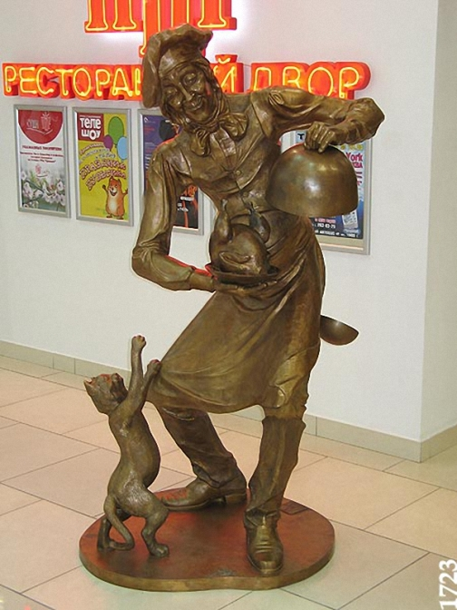 "Ivory sculpture of cat and cook in Yekaterinburg. The sculpture was installed in the shopping mall ""Greenwich"" Yekaterinburg. Author of composition – sculptor S.B. Belyaev"