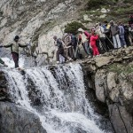 Brave Hindu pilgrims cross a waterfall as they make their pilgrimage to the sacred Amarnath Cave