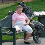 Maryland, USA. The Cat of the human life-size sitting on a bench holding out his paw as if to embrace anyone who wants to sit next to him