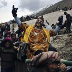 an Indian Hindu Holy man gestures to well-wishers as he is carried down a trail during the traditional journey to the Amarnath cave, near Panitarni