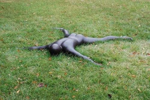 Weird sculpture of a man in the grass. Japanese Open-Air Art Museum