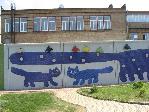 Blue cats decorate the fence. Landscape alley urban project by sculptor Konstantin Skretutsky