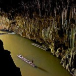 Shan Man Ong, standing on a bamboo raft, explores the downstream entrance of Tham Lod cave in Pang Mapha, Thailand.