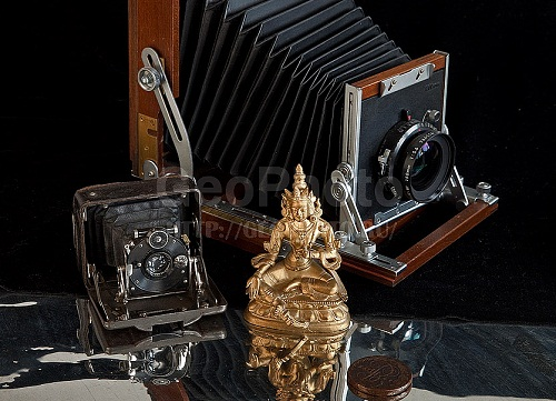 Buddha copper sculpture and Vintage camera. Work by Russian photographer Alexander Knyazev
