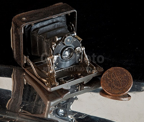 Old coin and vintage camera. Work by Russian photographer Alexander Knyazev