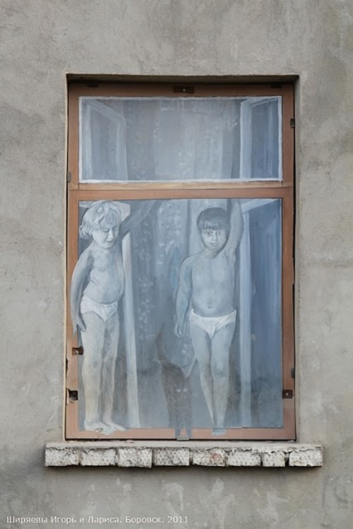 A girl and a boy standing on the window
