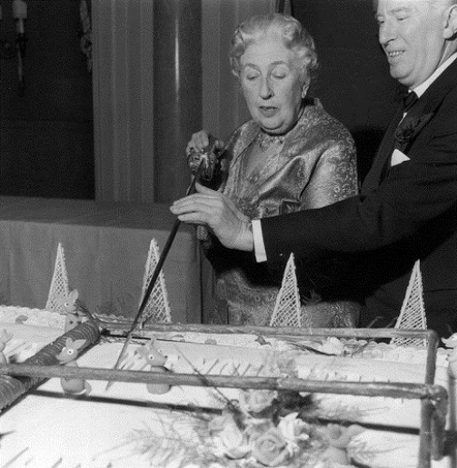 26th November 1962. Mystery writer Agatha Christie (1890 – 1976) cuts an enormous cake at a party to celebrate the 10th anniversary of her long-running play, 'The Mousetrap'