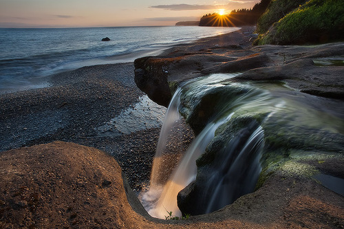 The last rays of the day set over Sandcut beach and waterfalls located on the west coast of Vancouver Island
