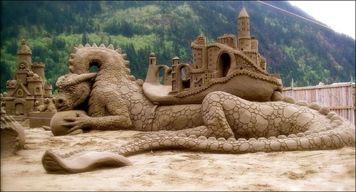 A dragon with a castle on its body. Fabulous sand sculpture made during the International art festival