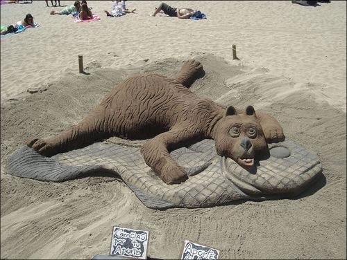 Sunbathing bear, funny sand sculpture