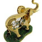 Gold ELEPHANT with Swarovski Crystals, with a splendid 24k gold finish and four dazzling Swarovski crystals placed in its sides. It stands on an irregularly shaped base with textured enamel coated surface that resembles turf