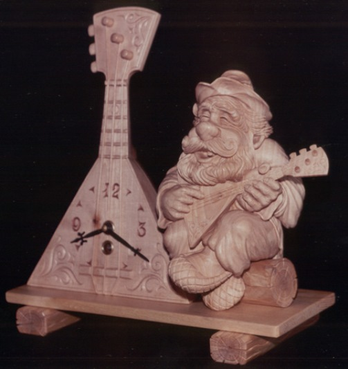 Playing balalaika. Wood sculpture from 'Hours of Russian soul' collection by Yuri Firsanov