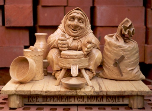 Old woman – potter. Wood sculpture by Yuri Firsanov