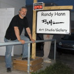 American self-taught artist Randy Hann standing next to his art studio