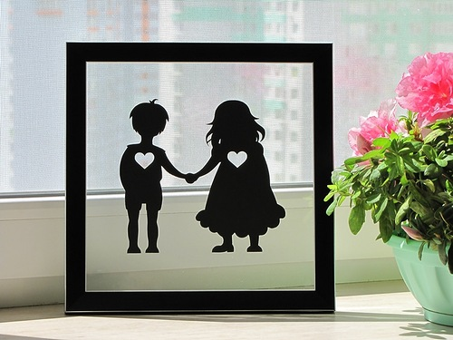 Little girl and boy holding their hands together. Paper silhouette by artists Dmitry and Julia