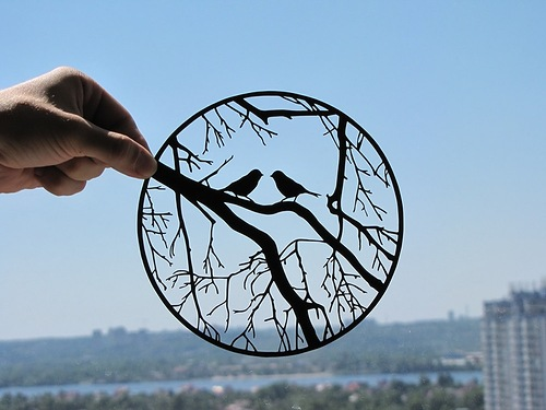 Beautiful paper silhouette of two birds sitting on a branch. Artists Dmitry and Julia