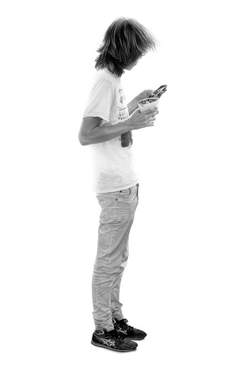 A young man with a mobile phone. Hyper realistic Graphite on paper drawing by Canadian artist Brian Boulton