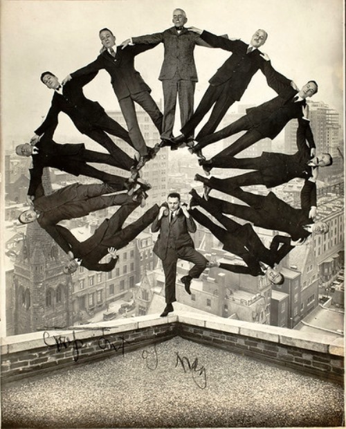 Trick photo of man standing on edge of building with 11 men in formation on his shoulders