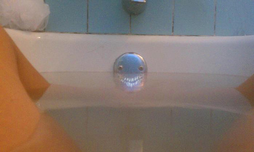 Ominously hiding teeth below the water. Weird face in the bath