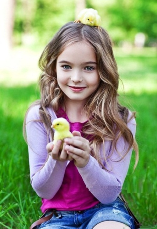 Holding a chicken in her hand and on the head Anastasia Bezrukova, beautiful Moscow based 8-year-old child model
