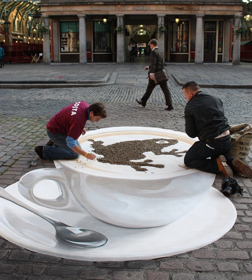 Incredibly realistic picture of a cup of coffee on asphalt. 3-D illusion by German artist Manfred Stader