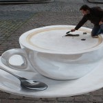 Work in progress. A cup of coffee. 3-D illusion, street art by German artist Manfred Stader