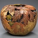 Carving on pumpkin. Autumn leaves vase by American artist Marilyn Sunderland
