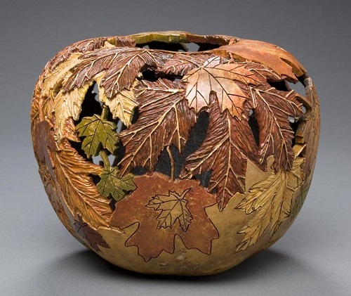 Carving on pumpkin. Autumn leaves vase by American artist Marilyn Sunderland