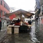 A fruit stand at a local market is seen in a flooded street during a period of seasonal high water in Venice November 1, 2012