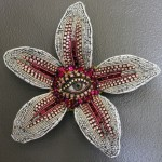 A flower with an eye in the center. Jewelry sculpture covered with mosaic of bead by American artist jeweler Betsy Angkvist