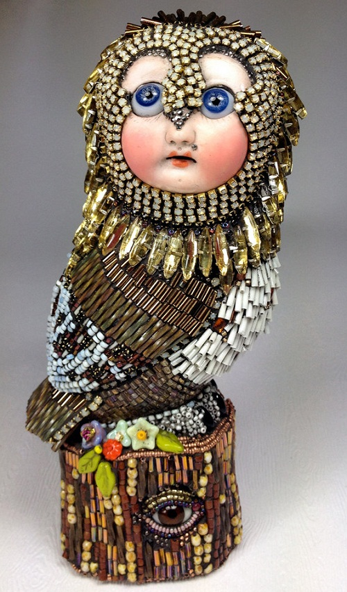 Owl Sculpture with a doll face. And even stump on which it sits, has an eye. Surreal bead sculpture by creative American artist Betsy Youngquist